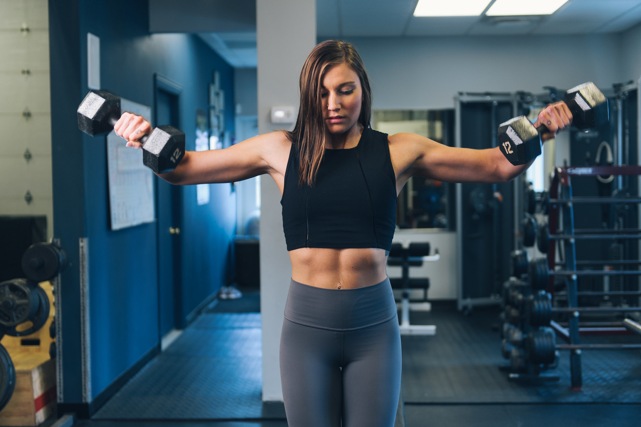 female trainer lifting dumbbells in a gym